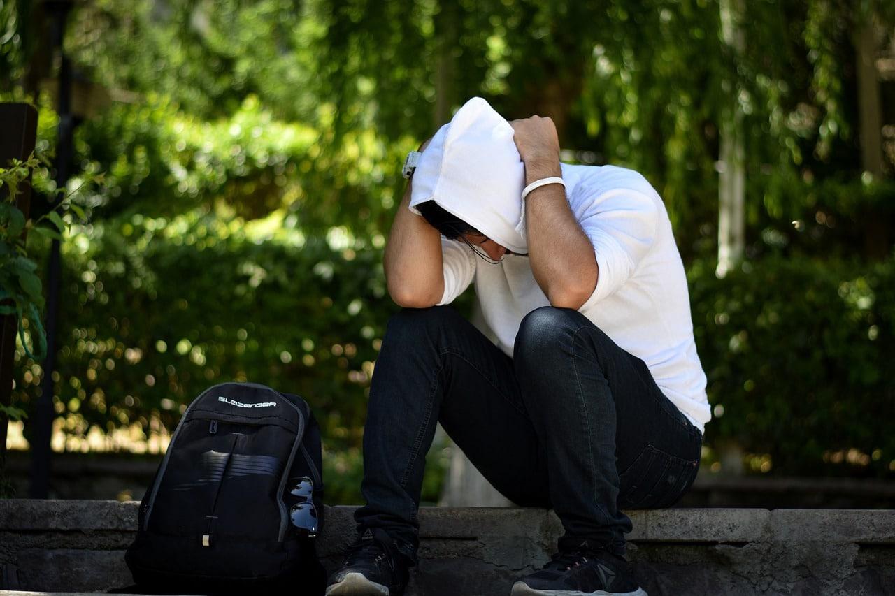 אדם יושב עם חולצה לבנה שסובל מדיכאון כתוצאה מעבודה